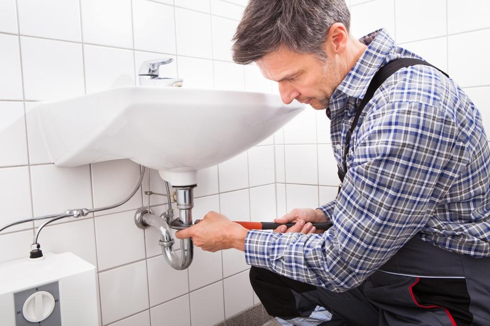 Plumber installing sink
