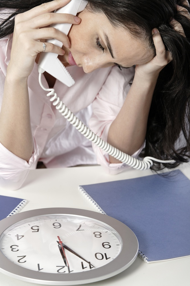 Woman on the phone watching a clock with a deadline approaching.jpeg